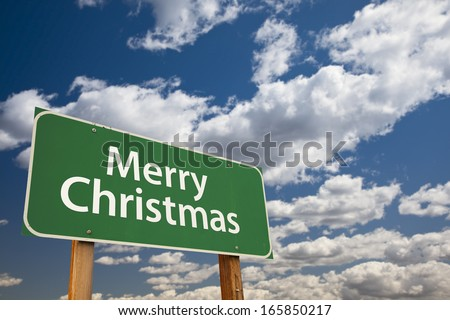 Merry Christmas Green Road Sign Over Dramatic Clouds and Sky.