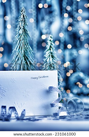 Merry Christmas greeting card, little decorative fir tree and silver ribbon on blur lights background, beautiful festive still life  - stock photo