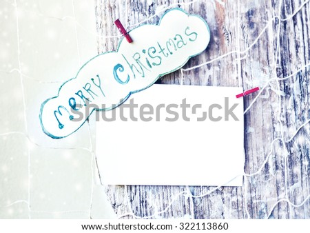 Merry Christmas greeting message on wooden background, Paper tag with strings, wishing a Merry Christmas, over old wood surface. Retro style Christmas background with copy space - stock photo