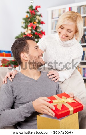 Merry Christmas! Handsome young man sitting on the couch and holding a gift box while her girlfriend standing behind him and smiling