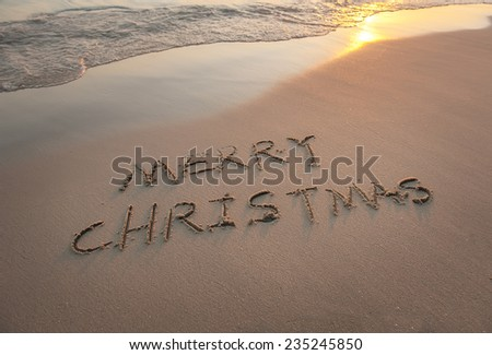 Merry Christmas handwritten in sand on beach - stock photo