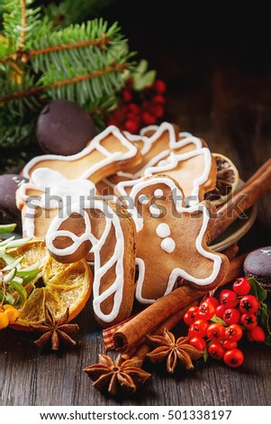 Merry christmas holiday decoration background with ginger man snowflakes snowman and tree cookies. Cinnamon, dry orange, cardamom, star, makarones, fir-tree branch, berries. Dark wooden table