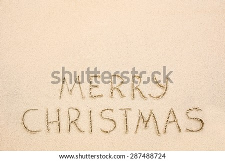 Merry Christmas inscription on wet yellow shoreline beach sand. Holiday wish message - stock photo