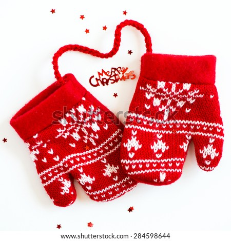 Merry Christmas letters, little Stars and Red Knitted Mittens with Snowflake Motives on white background - stock photo