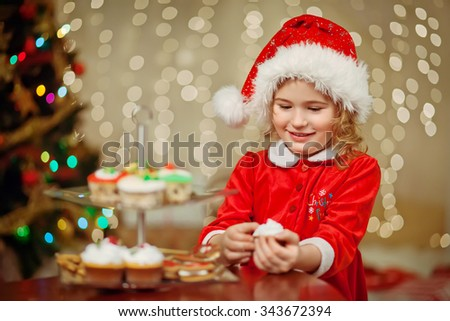 Merry Christmas - Little pretty girl in hat holding plate with cookies and candy - stock photo