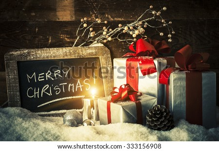 Merry Christmas on a slate with gifts and candle. - stock photo