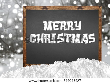 Merry Christmas on blank blackboard with blurr forest and snow