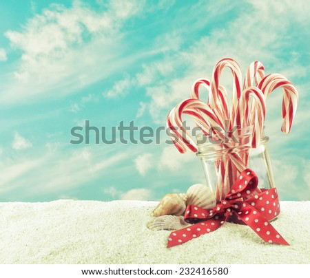 Merry Christmas on the Beach with Jar of Candy Canes on a sand and sky background with room or space for copy, text, your words.  Horizontal, can crop to vertical, instagram vintage, warm tone - stock photo