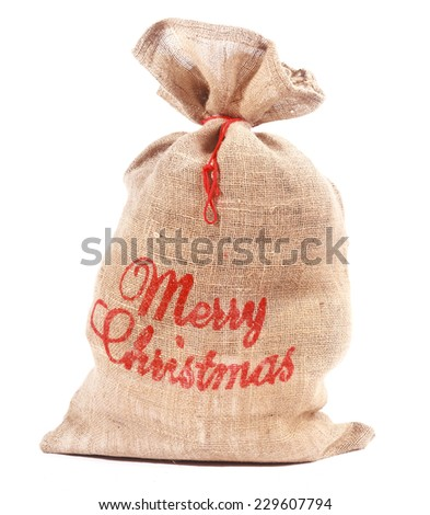 Merry Christmas rustic hessian sack full of gifts with a red Christmas greeting on the side tied with string over a white background - stock photo