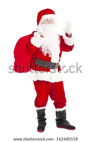 merry Christmas Santa Claus holding gift bag with ok gesture - stock photo