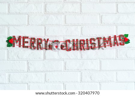 Merry Christmas sign hanging on white brick wall as decoration - stock photo