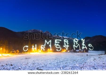 Merry Christmas sign under Tatra mountains at night, Poland - stock photo