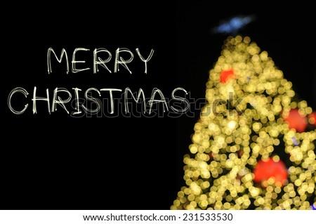Merry Christmas sparkle firework with bokeh unfocused Christmas tree - stock photo