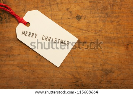 Merry Christmas tag on old wooden surface. - stock photo