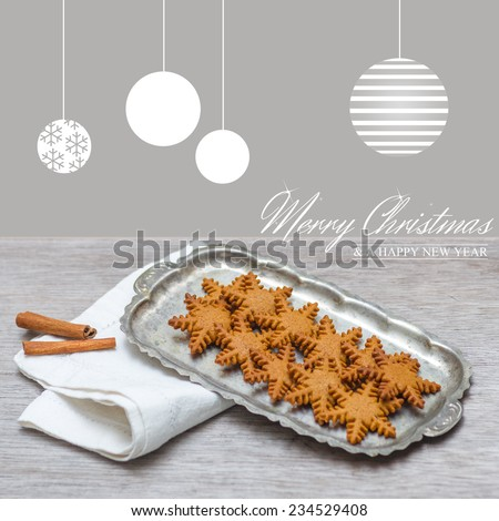 Merry Christmas text. Merry Christmas card with  decoration hanging on top of gingerbreads. Selective focus on handmade ginger bread. Square card. - stock photo