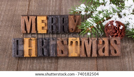 Merry Christmas text on a wooden surface with snowy tree branch and pinecone