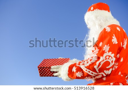Merry Christmas with joyful Santa Claus ready to ship and delivering gift packages on sunny blue sky outdoors background. Happy time for amazement and excitement
