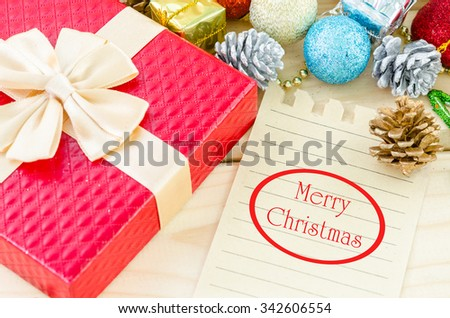 Merry Christmas word writing on brown paper with christmas decorations on wooden background. - stock photo