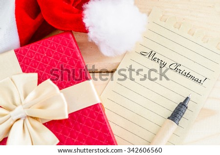 Merry Christmas word writing with pen on brown paper with red gift box on wooden background.
