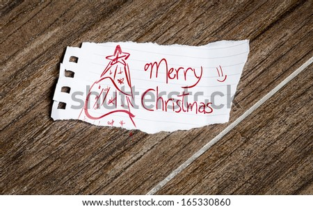 Merry Christmas written on the paper on a wood background - stock photo