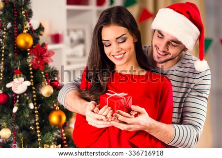 Merry Christmas. Young couple celebrating Christmas at home - stock photo