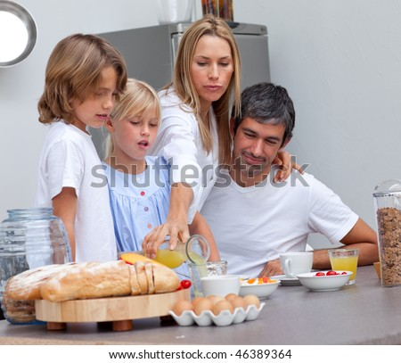 Merry family having breakfast in the kitchen - stock photo