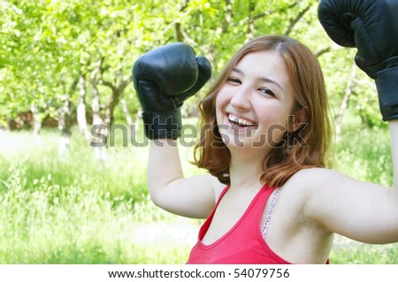 merry girl in boxing-gloves on nature - stock photo