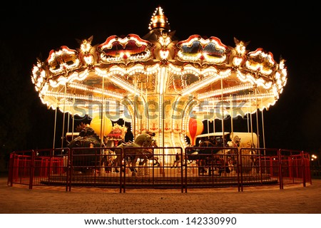Merry-Go-Round (carousel) illuminated at night. The picture was taken near Paris, France - stock photo