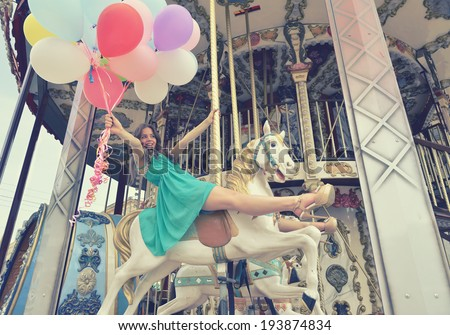 Merry-go-round young woman playing on carousel, toned. - stock photo