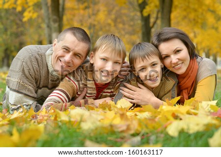 merry happy family on a walk during the fall of the leaves in the park