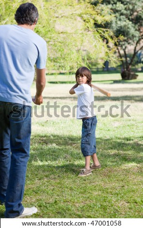 Merry little boy playing baseball with his father in the park - stock photo