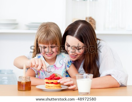 Merry little girl and her mother having breakfast in the kitchen