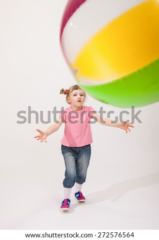 Merry little girl with a big ball on neutral background - stock photo