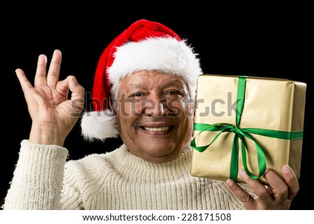 Merry male senior with broad grin and almost tears in eyes with happiness. Raising a wrapped golden gift in his left hand, while gesturing the OK sign with his right. Red Santa Claus cap. Cut-out. - stock photo