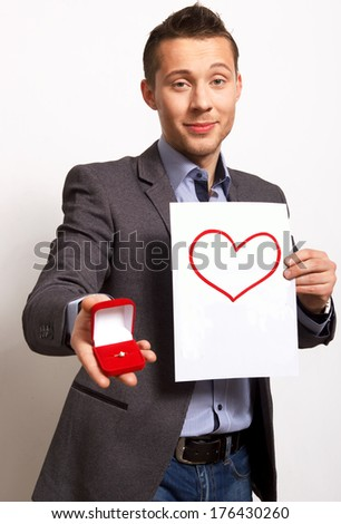 Merry proposal.young man holds out the engagement ring to the camera - stock photo