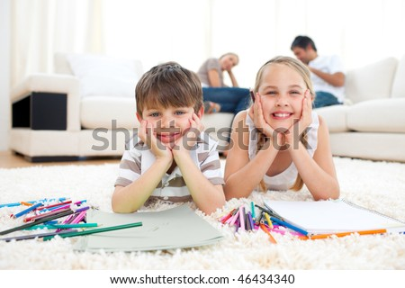 Merry siblings drawing lying on the floor in the living room
