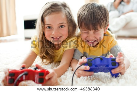 Merry siblings playing video game in the living room - stock photo