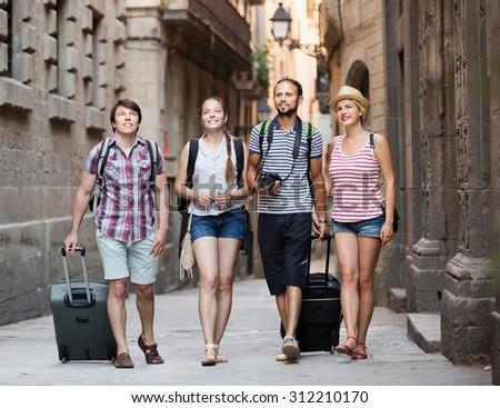 Merry travelers walking the street and watching landmark  - stock photo