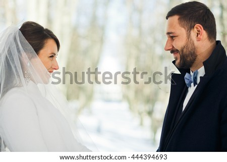 Merry wedding couple stands in winter coats during the ceremony outside