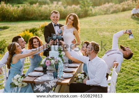 Merry wedding in nature. Guests with the bride and groom are celebrating at the table