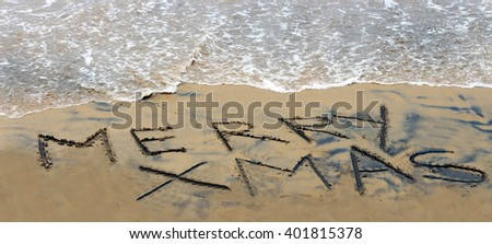Merry xmas handwritten in sand. A summer Christmas in the Southern Hemisphere. - stock photo