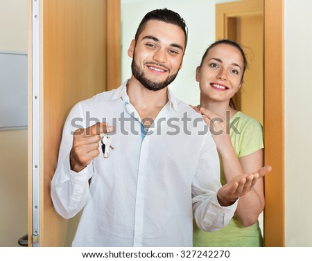 Merry young couple coming to the apartment