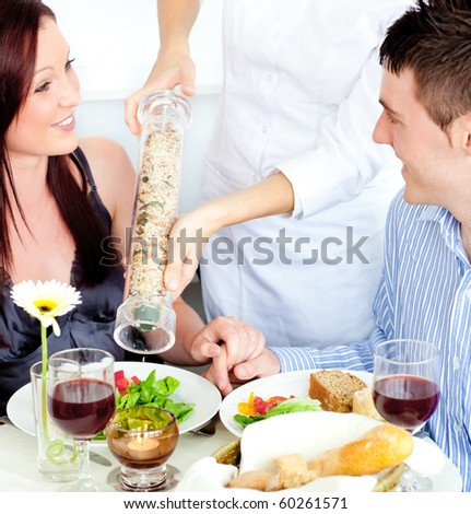 Merry young couple dining at the restaurant with waiter putting pepper in their plate