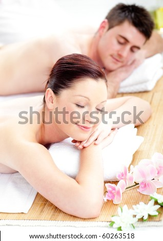 Merry young couple receiving a back massage in a spa center - stock photo