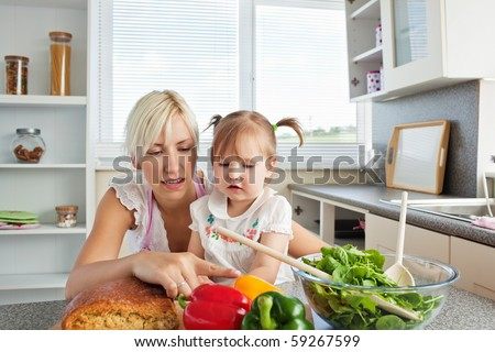 Merry young family preparing a salad in the kitchen - stock photo