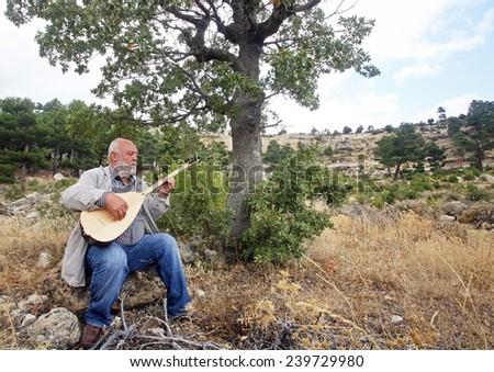 MERSIN, TURKEY - OCTOBER 15: Famous Turkish Turkish folk musician and Turkish instrument baglama virtuoso Musa Erolu portrait on October 15, 2009 in Mersin, Turkey. - stock photo