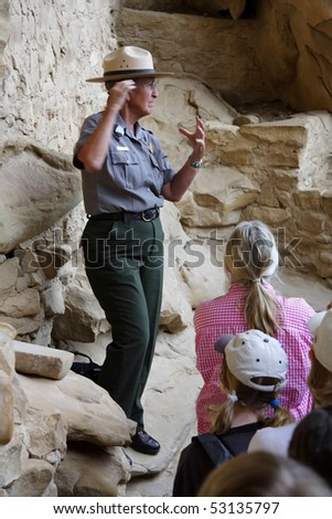 MESA VERDE, CO - JULY 26: A Park Ranger leads visitors on an educational tour through Cliff Palace in Mesa Verde National Park July 26, 2008 in Mesa Verde, CO. - stock photo