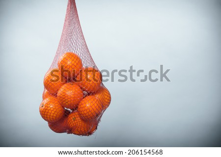 Mesh bag of fresh oranges healthy tropical fruits from supermarket on gray. Food retail. - stock photo