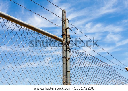 Mesh fence with barbed wire on a background of blue sky