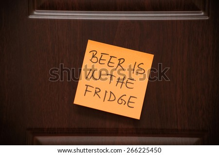 """Message """"Beer is in the Fridge"""" handwritten on the sticky note on the wooden door - stock photo"""